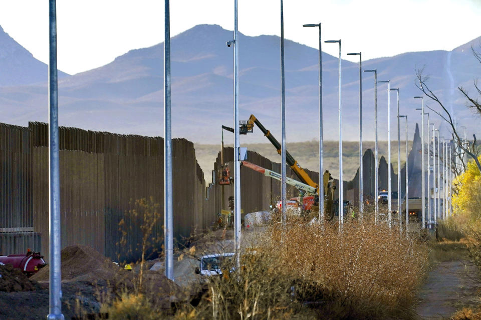 Crews construct a section of border wall in San Bernardino National Wildlife Refuge, Tuesday, Dec. 8, 2020, in Douglas, Ariz. Construction of the border wall, mostly in government owned wildlife refuges and Indigenous territory, has led to environmental damage and the scarring of unique desert and mountain landscapes that conservationists fear could be irreversible. (AP Photo/Matt York)