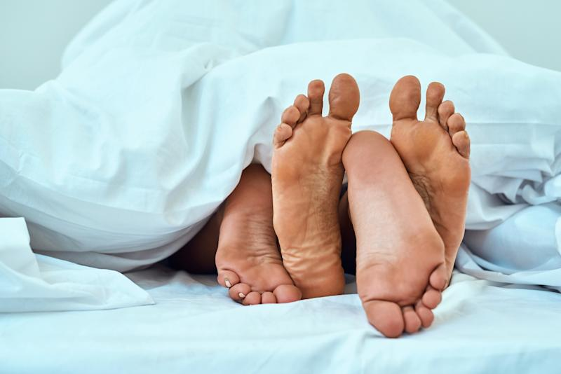 Two pairs of feet poking out from under bed sheets.