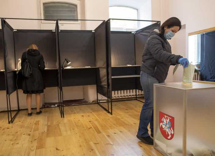 A woman, wearing a face mask to protect against coronavirus, casts her ballot at a polling station during parliamentary elections in Vilnius, Lithuania, Sunday, Oct. 11, 2020. Polls opened Sunday for the first round of national election in Lithuania, where voters will renew the 141-seat parliament and the ruling four-party coalition is widely expected to face a stiff challenge from the opposition to remain in office. (AP Photo/Mindaugas Kulbis)