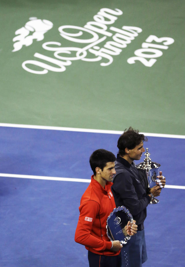 Novak Djokovic, of Serbia, left, and Rafael Nadal, of Spain, pose for photos after Nadal beat Djokovic in the men's singles final of the 2013 U.S. Open tennis tournament, Monday, Sept. 9, 2013, in New York. (AP Photo/Julio Cortez)