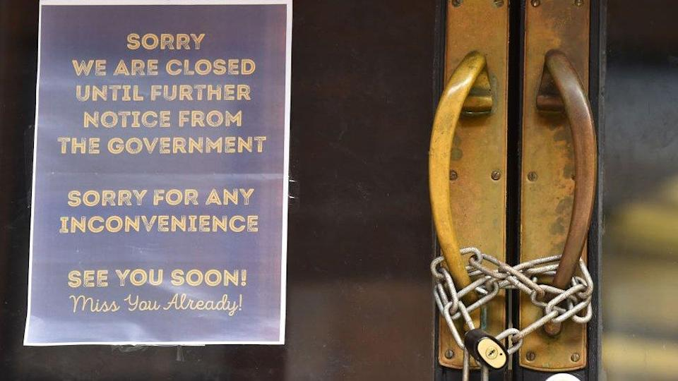 A locked shop displays a sign saying 'sorry we are closed until further notice from the Government, sorry for any inconvenience, see you soon