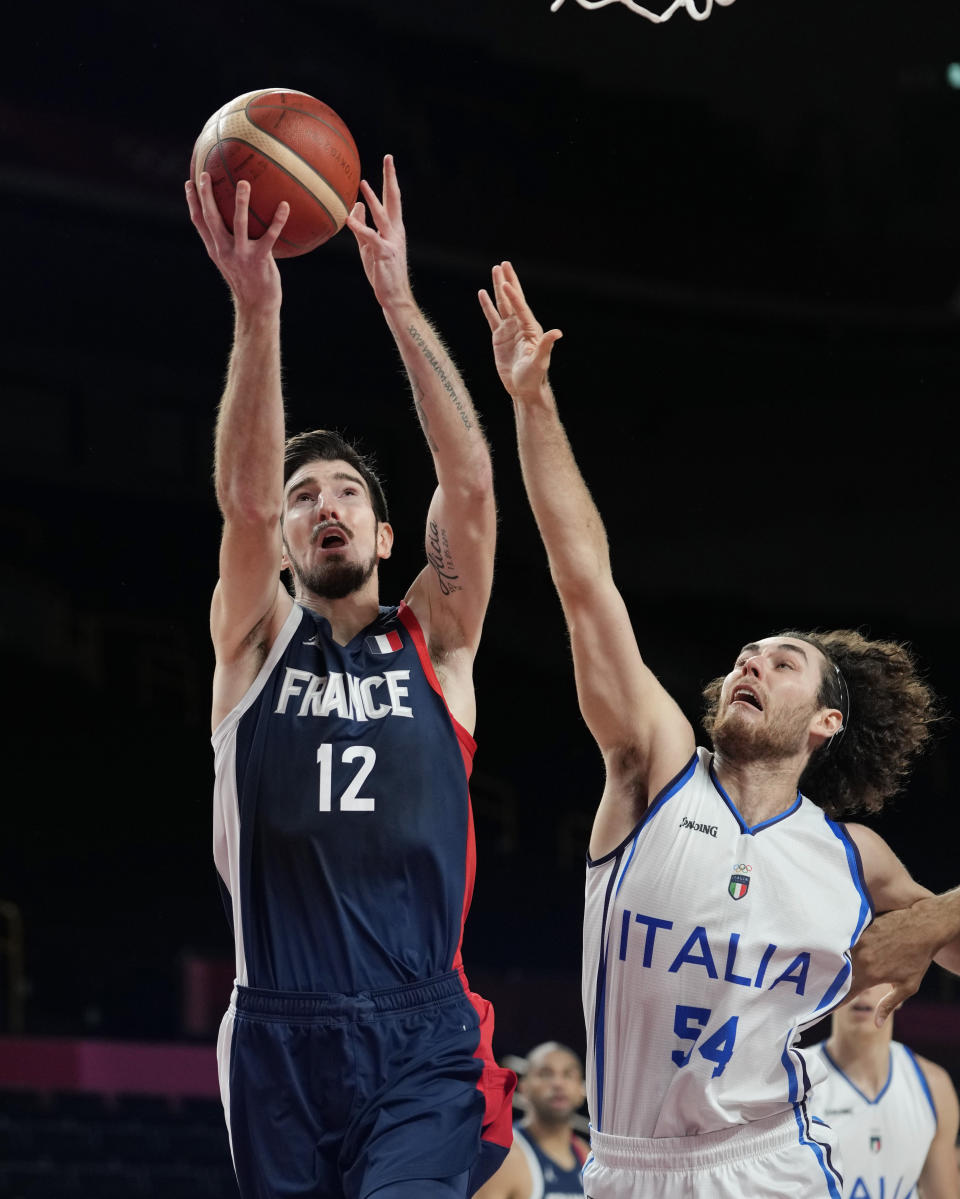 France's Nando de Colo (12) scores over Italy's Alessandro Pajola (54) during a men's basketball quarterfinal round game at the 2020 Summer Olympics, Tuesday, Aug. 3, 2021, in Saitama, Japan. (AP Photo/Eric Gay)