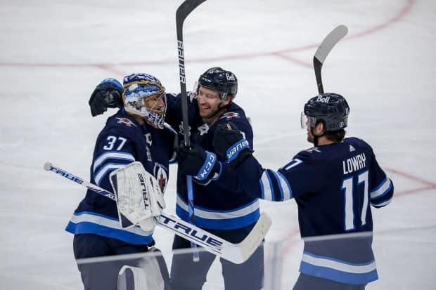 A cast of first-round playoff heroes emerged for the Jets during their first-round series sweep of the Oilers, including centre Adam Lowry, right, andnetminder Connor Hellebuyck, who allowed just eight goals on 159 shots for a .950 save percentage.  (Jonathan Kozub/NHLI via Getty Images - image credit)