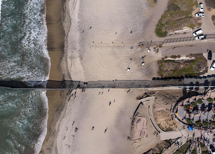<p>Aerial view of the US (above).-Mexico (below) border divided by the border fence in Playas de Tijuana, Mexico, on Nov.14, 2018, as a group of Central American migrants moving towards the United States in hopes of a better life,stayed around on the Mexican side. (Photo: Guillermo Arias/AFP/Getty Images) </p>