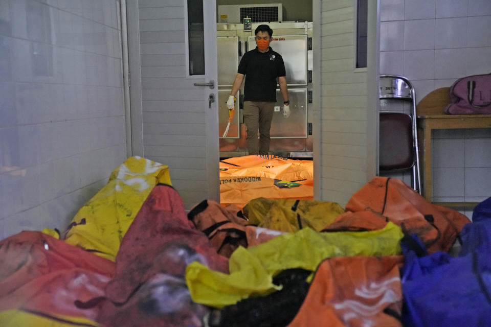A member of police forensic team stands near body bags containing the bodies of the victims of a prison fire at the local hospital's morgue in Tangerang on the outskirts of Jakarta, Indonesia, Wednesday, Sept. 8, 2021. A massive fire raged through an overcrowded prison near Indonesia's capital early Wednesday, killing a number of inmates. (AP Photo/Dita Alangkara)