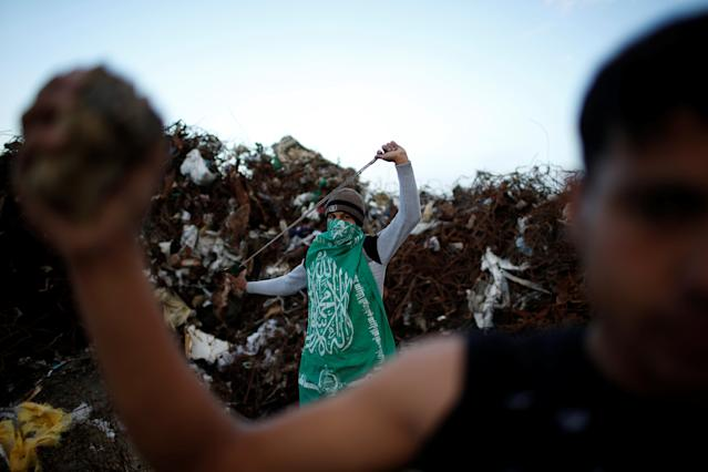 """<p>A Palestinian protester, nicknamed Abu Akram, wearing a Hamas flag, holds a sling as he poses for a photograph at the scene of clashes with Israeli troops near the border with Israel, east of Gaza City, Jan. 19, 2018. """"We are here to protest against the Israeli blockade on Gaza which led to the deterioration of the economic situation, and to show our commitment to defend Jerusalem. We hope that the blockade on Gaza will be lifted soon,"""" said Abu Akram. (Photo: Mohammed Salem/Reuters) </p>"""