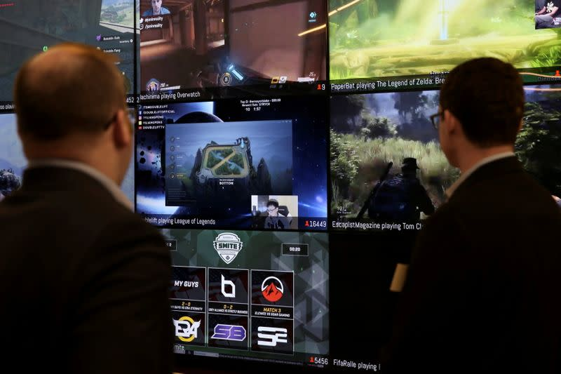 FILE PHOTO: Men look at a wall of real-time video game play in the lobby of Twitch Interactive Inc, a social video platform and gaming community owned by Amazon, in San Francisco, California