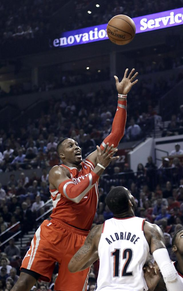 Houston Rockets center Dwight Howard, left, shoots over Portland Trail Blazers forward LaMarcus Aldridge during the first half of Game 3 of an NBA basketball first-round playoff series in Portland, Ore., Friday, April 25, 2014. (AP Photo/Don Ryan)