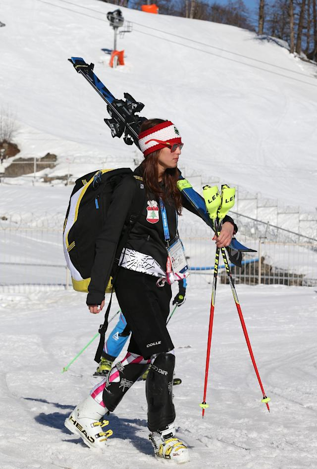 """Lebanon's Jacky Chamoun walks near the alpine ski course finish area at the Sochi 2014 Winter Olympics, Thursday, Feb. 13, 2014, in Krasnaya Polyana, Russia. The Lebanese Olympic skier seen topless in revealing photographs and a video that circulated on the Internet says her country's sports officials are """"on my side."""" Three years ago, Chamoun posed for a calendar photo shoot. Behind-the-scenes footage recently was posted online, and Lebanon's Sports and Youth Minister reportedly ordered an investigation. (AP Photo/Luca Bruno)"""