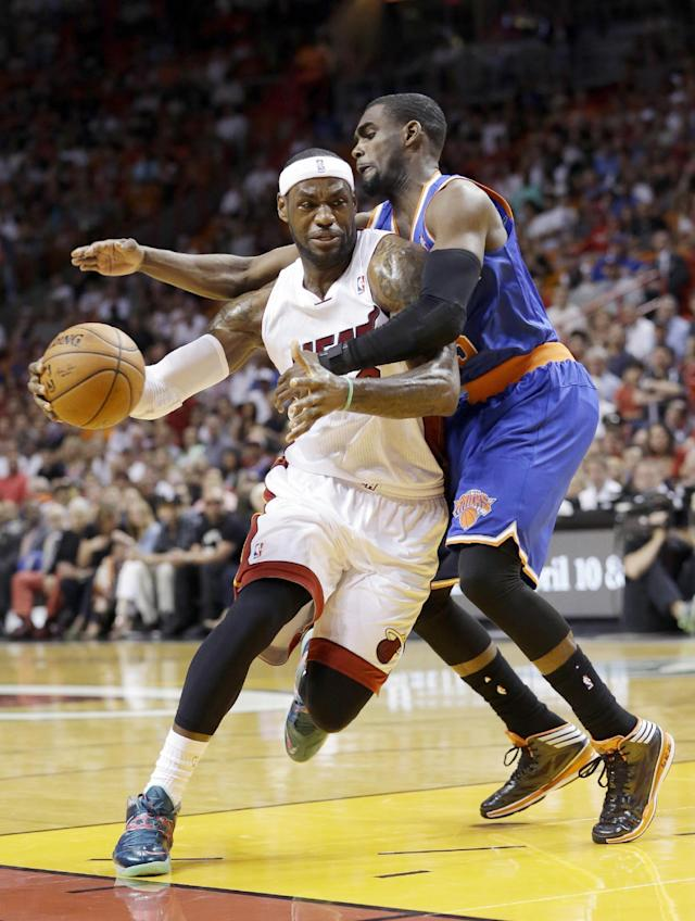 Miami Heat forward LeBron James is fouled by New York Knicks guard Tim Hardaway Jr., right, during the first half of an NBA basketball game, Sunday, April 6, 2014, in Miami. (AP Photo/Wilfredo Lee)