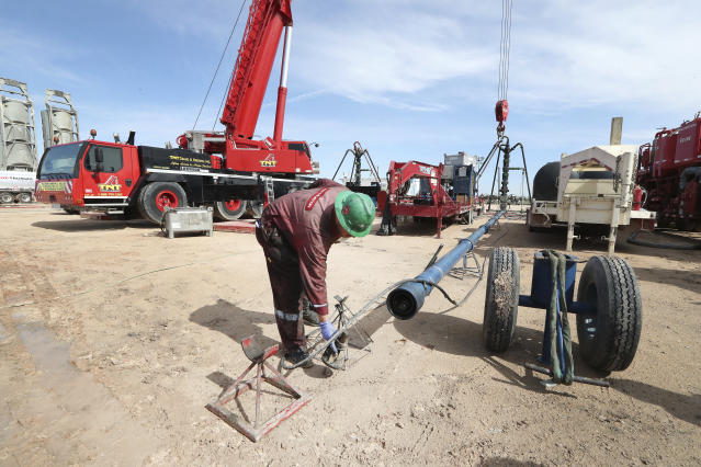 In a Monday, June 26, 2017 photo, Halliburton employees work at a three wellhead fracking site in Midland Texas. ( Steve Gonzales//Houston Chronicle via AP)