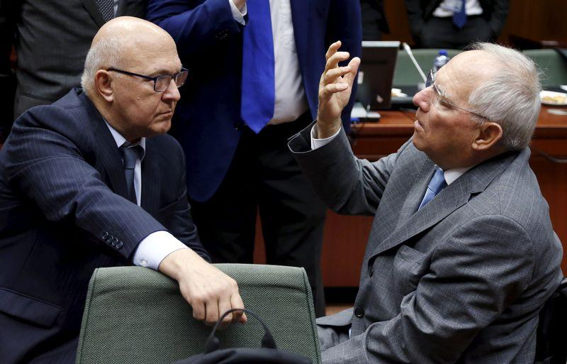 French Finance Minister Sapin listens to German counterpart Schaeuble during an EU finance ministers meeting in Brussels