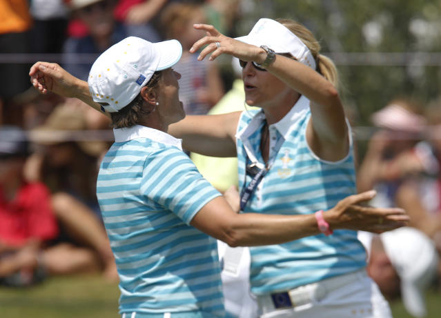 Europe's Catriona Matthew, left, from Scotland, is congratulated by assistant captain Carin Koch, Sweden, after Matthew and Caroline Masson, from Germany, halved their foursome match at the Solheim Cup golf tournament against the United States, Saturday, Aug. 17, 2013, in Parker, Colo. (AP Photo/Ed Andrieski)