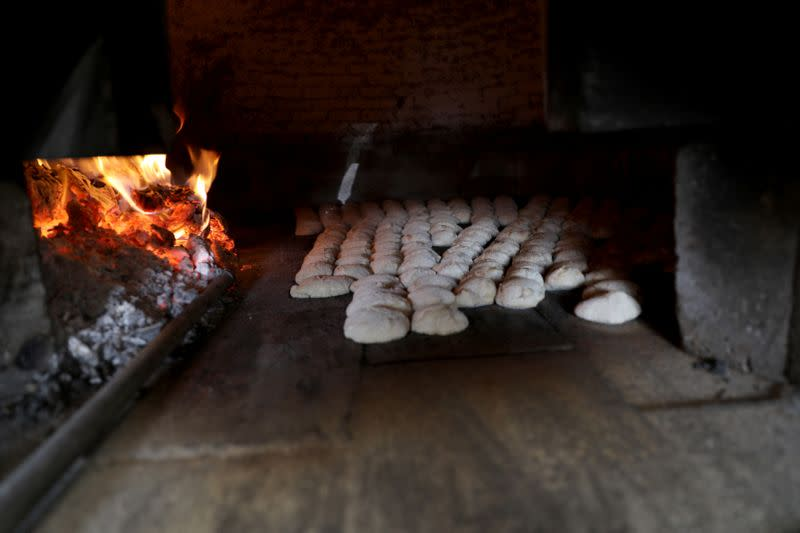 Bread is baked in a wood-fired oven due to fuel shorages in Sanaa
