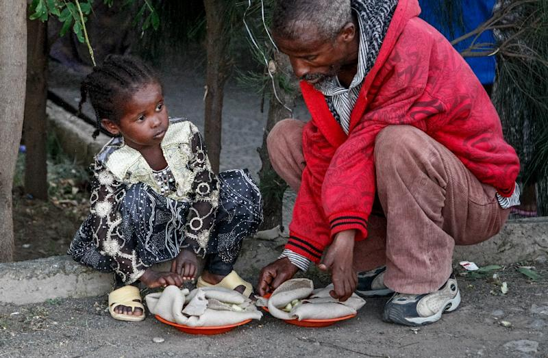 An Oromo girl sits next to a man as they eat donated food at a temporary camp for displaced people (AFP Photo/Paul Schemm)