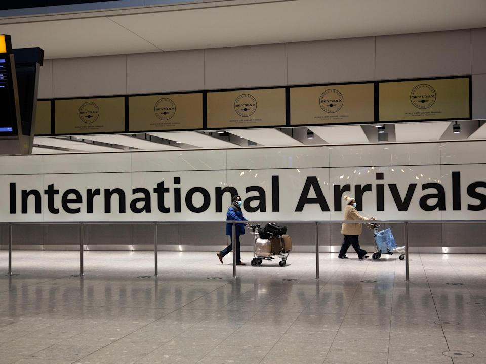 Arriving passengers walk past a sign in the arrivals area at Heathrow Airport in London in January during England's third national lockdown (AP)