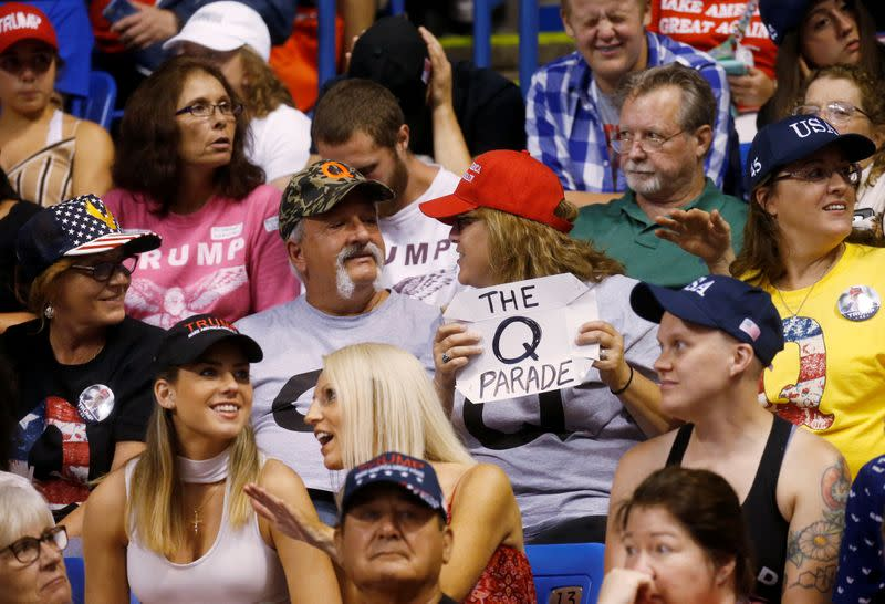 FILE PHOTO: A supporter holds a QAnon sign as U.S. President Donald Trump addresses a campaign rally at Mohegan Sun Arena in Wilkes-Barre, Pennsylvania