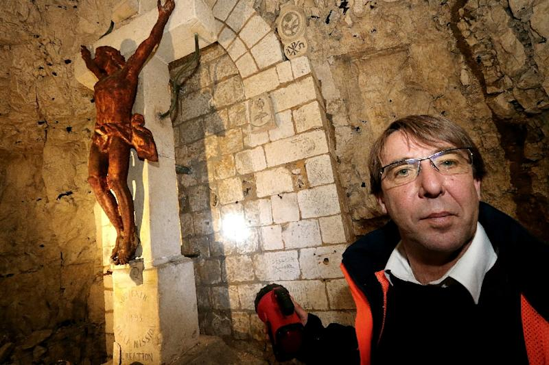 "Archaeologist Gilles Prilaux shines his torch on a crucifix in a chapel on April 21, 2016 in the ""underground city"" of Naours, France where some 3,000 graffiti inscriptions are being registered (AFP Photo/Francois Nascimbeni)"