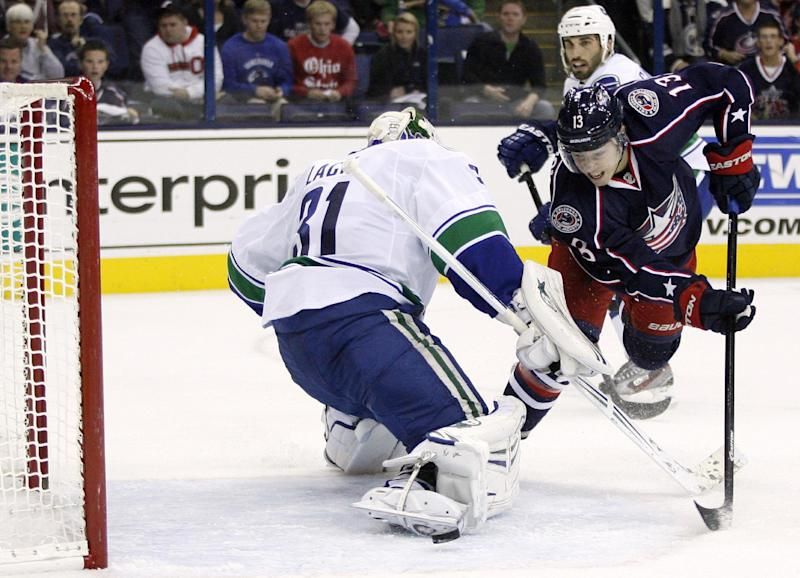 Columbus's Cam Atkinson, right, tries to get the puck past Vancouver goalie Eddie Lack (31) during the second period of an NHL hockey game Sunday, Oct. 20, 2013, in Columbus, Ohio. (AP Photo/Mike Munden)