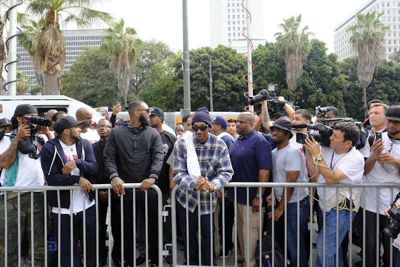 Rappers The Game, third from left, and Snoop Dogg, center, lead a march in support of unification outside of the graduation ceremony for the latest class of Los Angeles Police recruits in Los Angeles, Friday, July 8, 2016, after the shooting deaths of multiple police officers in Dallas on Thursday night. (AP Photo/Richard Vogel)