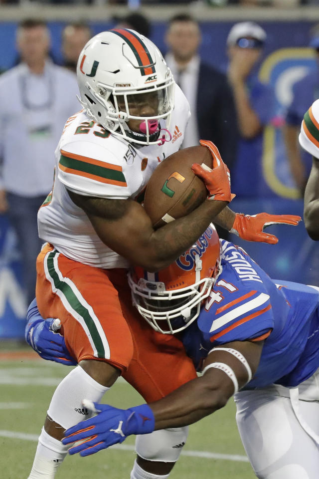 Miami running back Cam'Ron Harris, left, is stopped by Florida linebacker James Houston IV on a run during the first half of an NCAA college football game Saturday, Aug. 24, 2019, in Orlando, Fla. (AP Photo/John Raoux)