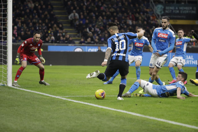 Inter Milan's Lautaro Martinez, with number 10, sets the ball up for Inter Milan's Romelu Lukaku who failed to score during an Italian Cup soccer match between Inter Milan and Napoli at the San Siro stadium, in Milan, Italy, Wednesday, Feb. 12, 2020. (AP Photo/Luca Bruno)