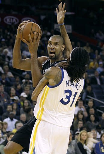 San Antonio Spurs center Tim Duncan, rear, looks for a shot against Golden State Warriors center Mikki Moore (31) during the first quarter of an NBA basketball game in Oakland, Calif., Monday, April 16, 2012. (AP Photo/Jeff Chiu)