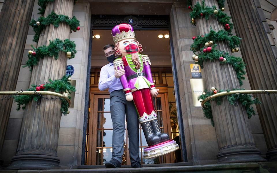 Guest services manager Bryan Tali places a model of a Christmas Nutcracker, complete with protective facemask, outside the entrance to the Kimpton Blythswood Square Hotel in Glasgow - Jane Barlow/PA Wire