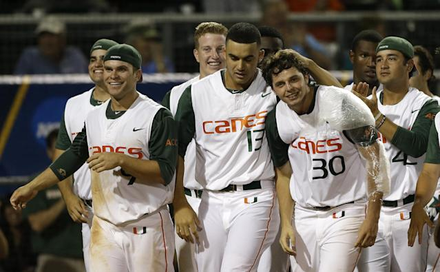 Miami's Andrew Suarez (30) is congratulated by teammates after ty defeated Bethune-Cookman in an NCAA college baseball regional tournament game in Coral Gables, Fla., Friday, May 30, 2014. Miami won 1-0. (AP Photo/Alan Diaz)