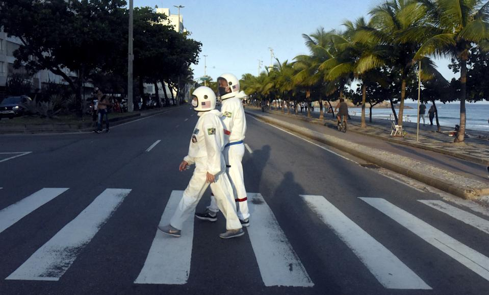 RIO DE JANEIRO, BRAZIL - JULY 21: People dressed as astronauts are seen amid coronavirus (Covid-19) pandemic along Ipanema beach in the south zone of Rio de Janeiro, Brazil on July 21, 2020. The outfit even has the NASA symbol and was created for trips around the city and the beach. Elderly with a chronic lung problem, retired accountant Tercio Galdino Lima, 66, decided to make the overalls and helmet for himself and his wife Alicea Lima, 65, to be able to walk more safely on the streets of Rio and reduce the risk of contagion by the coronavirus. Brazil has an average of 1,048 deaths per day from coronavirus in the last week. (Photo by Fabio Teixeira/Anadolu Agency via Getty Images)