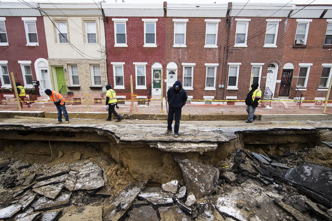 <p>Workers inspect a sinkhole in Philadelphia, Monday, Jan. 9, 2017. The Philadelphia Water Department said a water main break caused the sinkhole to open up on the street. (AP Photo/Matt Rourke) </p>