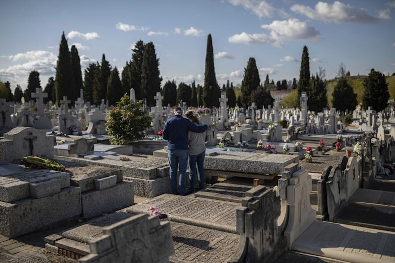 SPAIN: Two people at a Madrid cemetery.