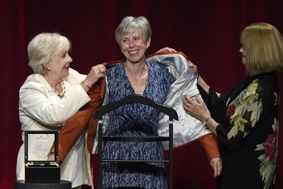 Three-time national coach of the year Barbara Stevens, center, is helped into her Hall of Fame jacket by her two sisters at the 2020 Basketball Hall of Fame awards tip-off celebration and awards gala, Friday, May 14, 2021, in Uncasville, Conn. (AP Photo/Kathy Willens)