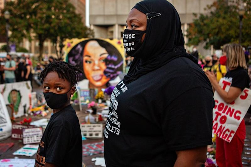 LOUISVILLE, KY - SEPTEMBER 26: A mother and son attends a demonstration in what is now called Injustice Square Park in downtown Louisville along with hundreds of others protesting a Kentucky grand jury's indictment of one of three police officers in the killing of Breonna Taylor, but not for her death on Saturday, Sept. 26, 2020 in Louisville, KY. (Jason Armond / Los Angeles Times)