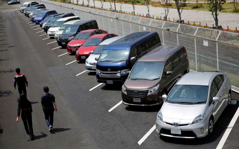 FILE PHOTO: People walk beside test-driving cars outside a car maker's showroom in Tokyo