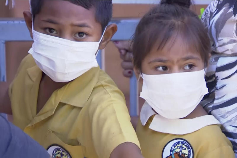 In this November 2019, image from video, masked children wait to get vaccinated at a health clinic in Apia, Samoa. Samoa closed all its schools on Monday, Nov.18, 2019, banned children from public gatherings and mandated that everybody get vaccinated after declaring an emergency due to a measles outbreak. For the past three weeks, the Pacific island nation of 200,000 people has been in the grip of a measles epidemic that has been exacerbated by low immunization rates. (TVNZ via AP)