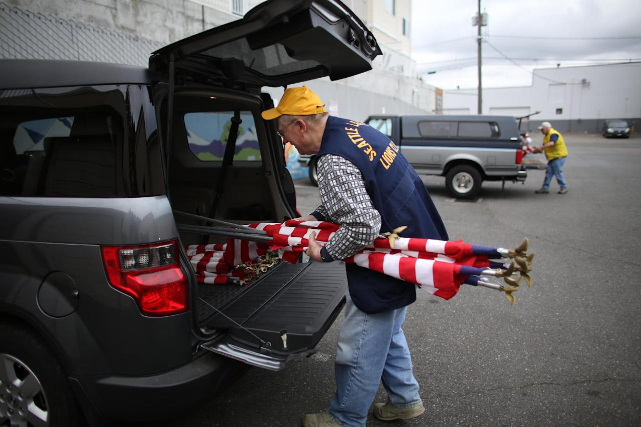Tom Lentz of Seattle's Lake City Lions Club gathers flags as a crew of Lions Club members head out to place flags on businesses in north Seattle and Shoreline on Flag Day, Friday, June 14, 2013. (AP Photo/seattlepi.com, Joshua Trujillo)