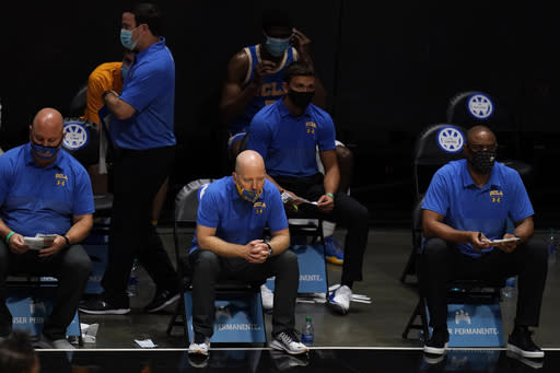 UCLA coach Mick Cronin, center, watches during the final minute of the team's NCAA college basketball game against San Diego State, Wednesday, Nov. 25, 2020, in San Diego. (AP Photo/Gregory Bull)