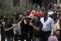 Palestinian mourners carry the body of Suha Jarrar, 30-year-old daughter of Khalida Jarrar, who is a prisoner in an Israeli jail, during her funeral, in the West Bank city of Ramallah, Tuesday, July 13, 2021. Khalida Jarrar, 58, a leading member of the Popular Front for the Liberation of Palestine, has been in and out of Israeli prison in recent years. Palestinian activists and human rights groups urged Israel to allow Jarrar to attend her daughter's funeral. (AP Photo/Majdi Mohammed)