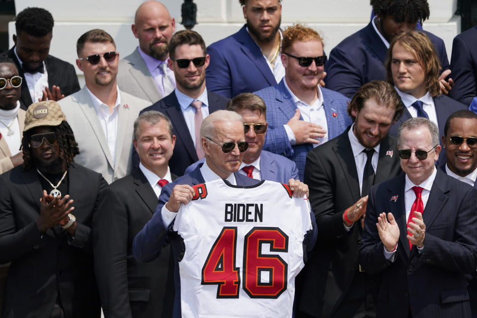 President Joe Biden, surrounded by members of the Tampa Bay Buccaneers, poses for a photo holding a jersey during a ceremony on the South Lawn of the White House, in Washington, Tuesday, July 20, 2021, where Biden honored the Super Bowl Champion Tampa Bay Buccaneers for their Super Bowl LV victory. (AP Photo/Andrew Harnik)