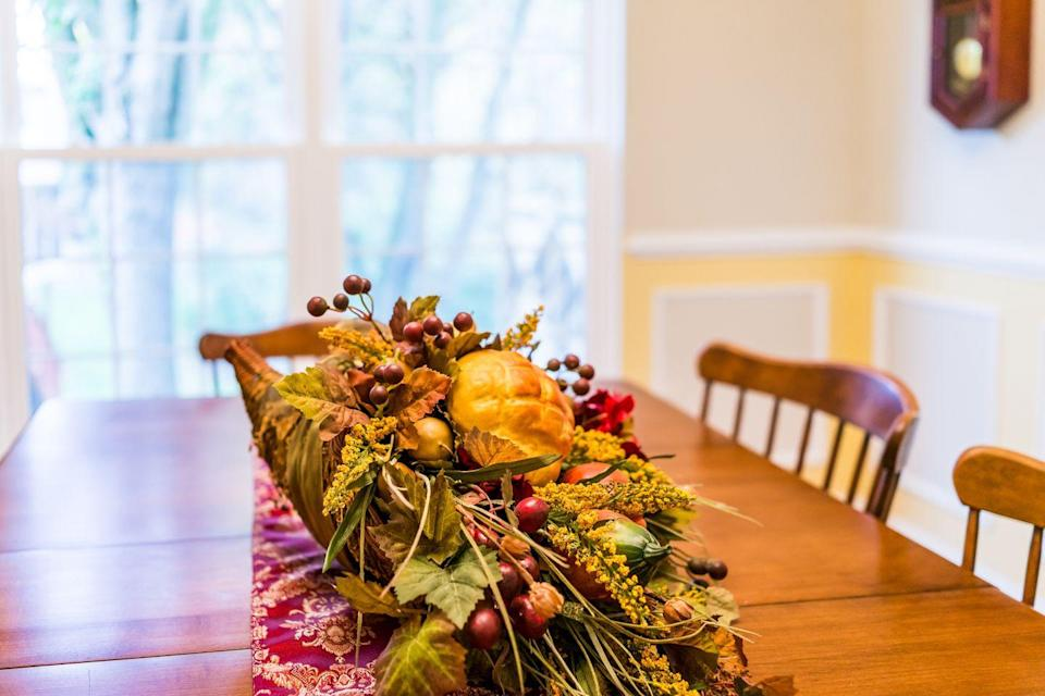 "<p>A traditional cornucopia is usually filled with the autumn harvest, seasonal plants and flowers, to show off that season's bounty. Put your own spin on it by asking your guests to bring objects that are meaningful to them, suggests Donelle Crigger of <a href=""https://gluesticksgumdrops.com/6-thanksgiving-traditions-start-family-year/"" rel=""nofollow noopener"" target=""_blank"" data-ylk=""slk:Gluesticks and Gumdrops"" class=""link rapid-noclick-resp"">Gluesticks and Gumdrops</a>. Place them in a cornucopia or a basket and use it as the centerpiece for your table as a visual reminder of what matters to those around the table. </p>"