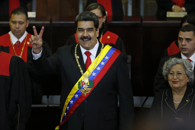 Venezuela's President Nicolas Maduro makes a victory sign during his swearing-in ceremony at the Supreme Court in Caracas, Venezuela, Thursday, Jan. 10, 2019. Maduro was sworn in to a second term amid international calls for him to step down and a devastating economic crisis. (AP Photo/Ariana Cubillos)