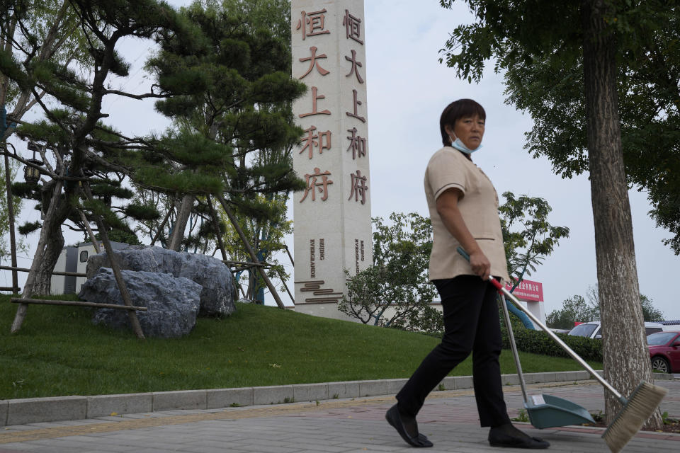 FILE - In this Sept. 15, 2021, file photo, a cleaner walks by the Evergrande's name and logo at its new housing development in Beijing. Global investors are watching nervously as one of China's biggest real estate developers struggles to avoid defaulting on tens of billions of dollars of debt, fueling fears of possible wider shock waves for the Chinese financial system. Chinese regulators have yet to say what they might do about Evergrande Group. (AP Photo/Andy Wong, File)