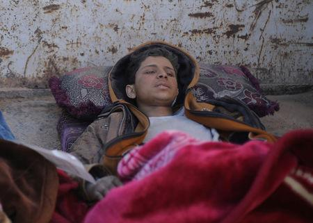 Hareth Najem, an Iraqi orphan lies under a blanket in a truck, near the village of Baghouz, Deir Al Zor province, Syria March 1, 2019. Picture taken March 1, 2019. REUTERS/Rodi Said