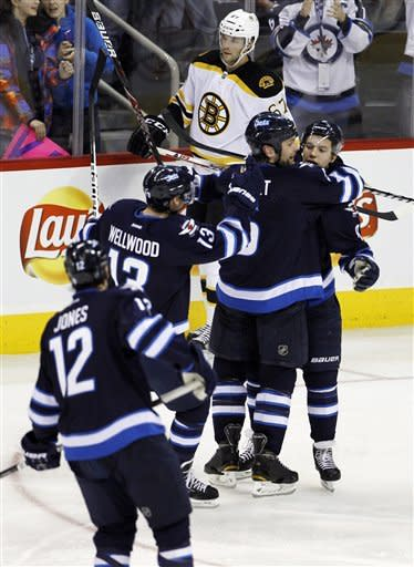 Winnipeg Jets' Randy Jones (12), Kyle Wellwood (13) and Mark Stuart (5) celebrate with Alexander Burmistrov (8) in front of Boston Bruins' Benoit Pouliot after scoring during the second period of an NHL hockey game, Friday, Feb. 17, 2012, in Winnipeg, Manitoba. (AP Photo/The Canadian Press, Trevor Hagan)