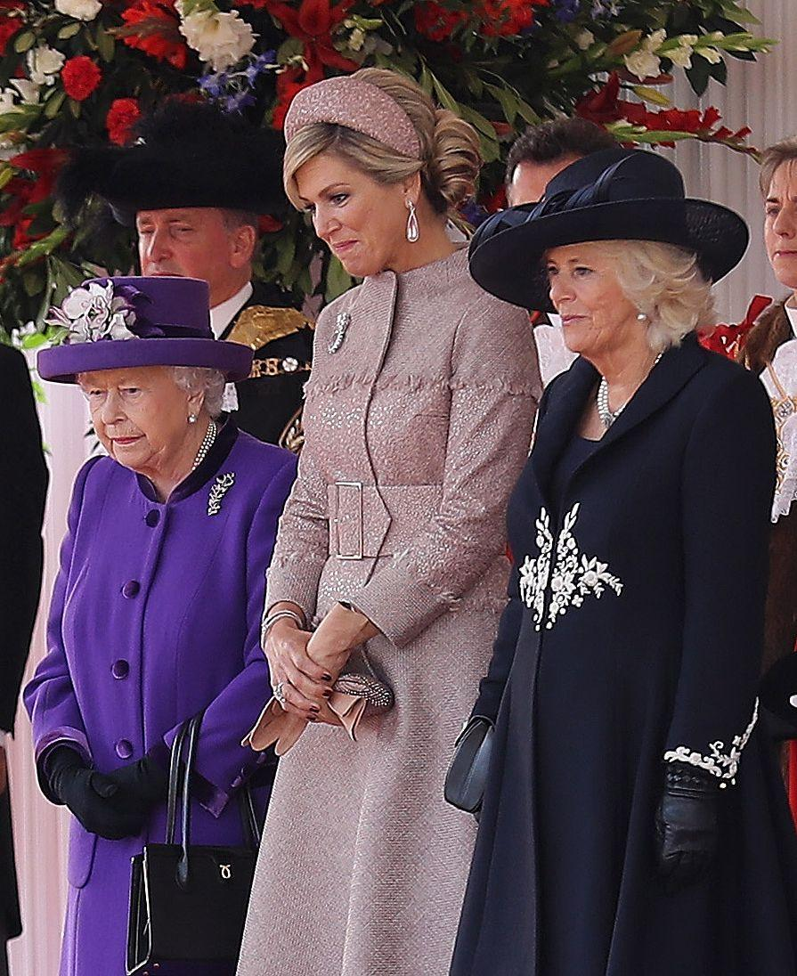 """<p>Camilla Parker Bowles wore a sleek black coat dress embellished with white floral detailing and a matching hat while greeting the <a href=""""https://www.townandcountrymag.com/society/tradition/g24107967/king-willem-alexander-queen-maxima-dutch-state-visit-uk-queen-elizabeth-photos/"""" rel=""""nofollow noopener"""" target=""""_blank"""" data-ylk=""""slk:King and Queen of the Netherlands"""" class=""""link rapid-noclick-resp"""">King and Queen of the Netherlands</a> during their visit to the UK.</p>"""