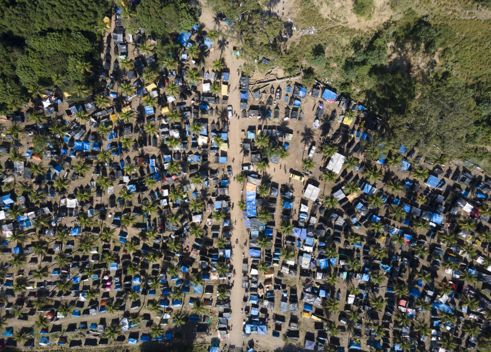 """FILE - In this May 26, 2021 file photo, tents and shacks cover land designated for a Petrobras refinery, called the """"First of May Refugee Camp,"""" which refers to the date the squatters camp sprung up amid the new coronavirus pandemic, in Itaguai, Rio de Janeiro state, Brazil. As Brazil hurtles toward an official COVID-19 death toll of 500,000, President Jair Bolsonaro has waged a campaign to downplay the virus's seriousness and keep the economy humming. (AP Photo/Mario Lobao, File)"""