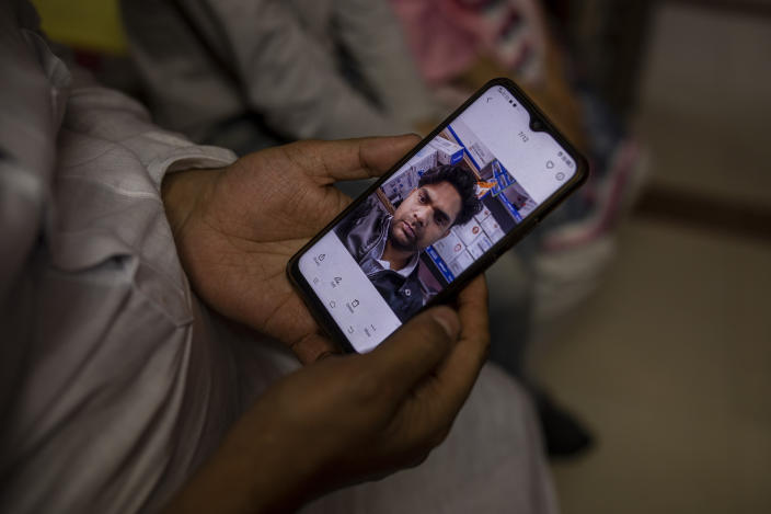 Haroon holds a mobile phone with a photograph of his 32 year-old brother who was shot and killed by his Hindu neighbors during the February 2020 communal riots, inside his home in North Ghonda, one of the worst riot affected neighborhood, in New Delhi, India, Friday, Feb. 19, 2021. As the first anniversary of bloody communal riots that convulsed the Indian capital approaches, Muslim victims are still shaken and struggling to make sense of their struggle to seek justice. (AP Photo/Altaf Qadri)