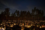 Relatives gather around some of the graves illuminated by candles during All Saints Day at the cemetery in Vilnius, Lithuania, Sunday, Nov. 1, 2020. Candles illuminated tombstones in graveyards across Europe as people communed with the souls of the dead on Thursday, observing one of the most sacred days in the Catholic calendar.(AP Photo/Mindaugas Kulbis)