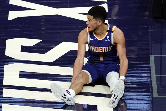 Phoenix Suns guard Devin Booker watches as play continues after he was knocked to the floor during the second half of the team's NBA basketball game against the Golden State Warriors on Thursday, March 4, 2021, in Phoenix. (AP Photo/Rick Scuteri)